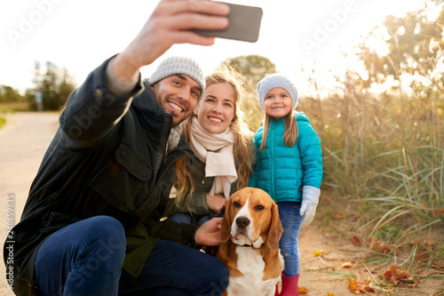 family, pets and people concept - happy mother, father and little daughter with beagle dog taking selfie by smartphone outdoors in autumn - 248659635
