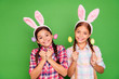 Leinwanddruck Bild - Close up photo of charming with beaming toothy smile white caucasian latin hispanic kids school girls holding colorful eggs in hands isolated bright vivid background