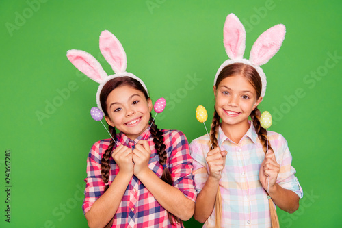 Leinwanddruck Bild Close up photo of charming with beaming toothy smile white caucasian latin hispanic kids school girls holding colorful eggs in hands isolated bright vivid background