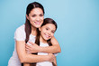 Leinwanddruck Bild - Close up photo pretty two people brown haired mum small little daughter best friends stand hugging piggy back lovely nice free time rejoice wearing white t-shirts isolated on bright blue background
