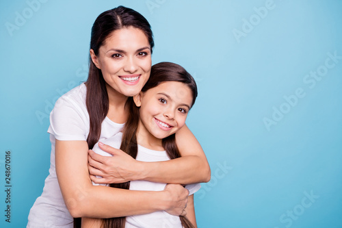 Leinwanddruck Bild Close up photo pretty two people brown haired mum small little daughter best friends stand hugging piggy back lovely nice free time rejoice wearing white t-shirts isolated on bright blue background