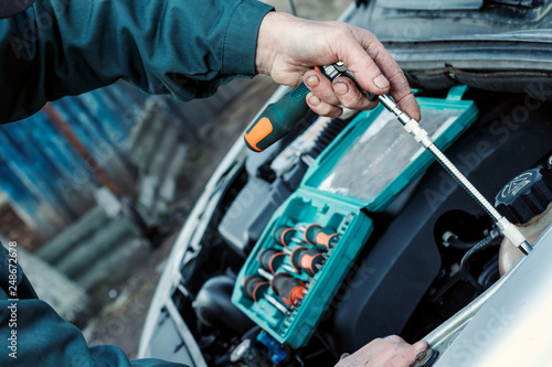 Wrench in male hand. Car service, engine repair, car repair shop. Hands of car mechanic in auto repair service.