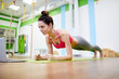 Full length portrait of strong young woman doing plank exercise during workout in fitness club, copy space