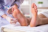 Podiatrist treating feet during procedure - 248681893