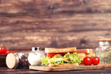 Tasty sandwich with fresh vegetables and spices on brown wooden table - 248685086