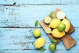 Lemons and limes with green leafs on blue wooden table