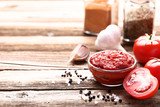 Ketchup in bowl with spices and garlic on wooden table - 248686845