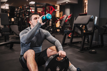 Muscular man drinking water while sitting on the floor in the gym.