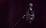 Close up studio condenser microphone with  anti-vibration mount live recording neon blue and pink lights