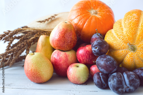 Foto Murales Still life of fresh fruit in a wicker basket and wheat.