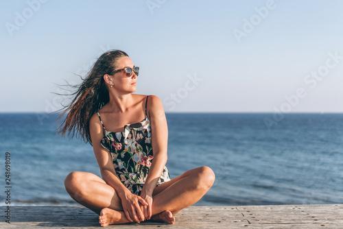 Pretty pan asian girl in dress sitting on the pier near sea. © bedya