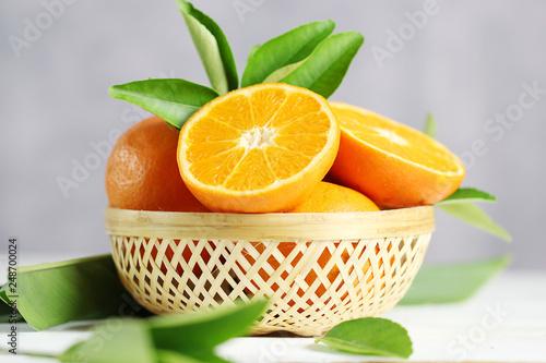Fresh oranges fruit in basket on white table background.