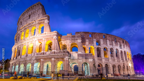 Roman Colosseum and tourists as night falls in Rome, Italy, blurred faces for commercial use