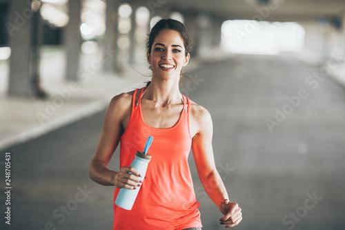 obraz lub plakat Female runner jogging trough parking lot.Fitness and jogging concept.