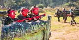 Opposing teams of happy kids shooting paintball