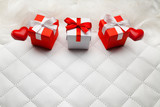 Three red gift boxes and red hearts on white leather background