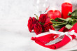 Holiday table setting with plate, roses and present.