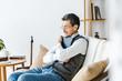 senior man in glasses hugging photo album while sitting on sofa