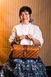 Femme assise avec un sac à main en osier
