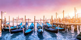 Majestic Gondolas in Venice at the sunset. Panoramic view of the San Giorgio Maggiore church from San Marco square. Travel and Vacation in Italy concept