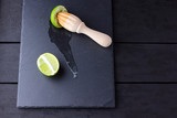 Lime halves and wooden juicer on slate board. Lime on black background. Fresh lime juice flows over the stone board. Healthy food