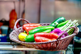 Red, green and yellow peppers are in the basket. - 248735471