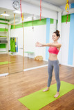 Full length portrait of cheerful young woman stretching arms during workout in fitness club, copy space