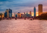 Beautiful panoramic view of the famous business buildings and river Thames illuminated at sunset, Cityscape of London in United Kingdom