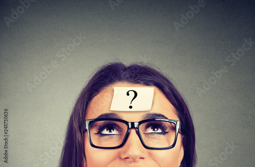 Leinwanddruck Bild thinking woman with question mark on gray wall background