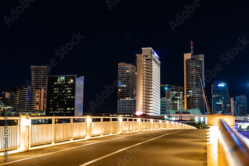 Crossing the bridge against the background of lighting skyscrapers