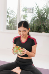 Young asian woman in fitness wear, with vegetarian healthy salad, sitting on floor, against white wall.