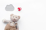 Baby care. Newborn baby concept. Teddy bear toy near pacifier on white background top view copy space