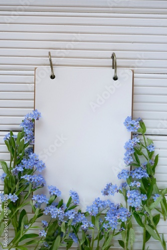 Foto Murales Spring to-do list.Spring Flower Mockup.Blank notepad in the forget-me-not flowers on a  wooden background.top view, copy space.