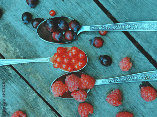 Foto Murales Spoon with different ripe berries. Raspberries on the table. Tasty fresh berries-viburnum, raspberry and Aronia melanocarpa (black chokeberry).Agriculture, Gardening, Harvest Concept.Selective focus.