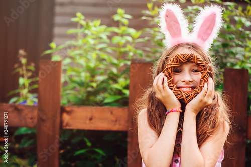Foto Murales easter portrait of happy child girl in funny bunny ears playing egg hunt outdoor at wooden country house