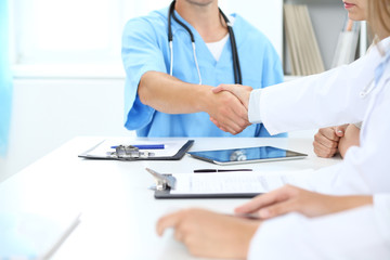 Doctors shaking hands to each other finishing up medical meeting