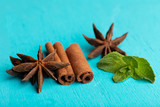 Sticks of cinnamon with mint sprig and anise stars on turquoise background. - 248810822