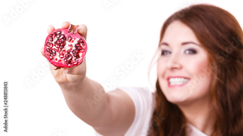 Foto Murales Cheerful woman holds pomegranate fruits, isolated