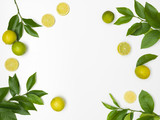 fresh, green limes with green twigs lie on a white background