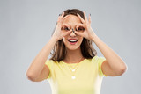 fun and people concept - smiling young woman or teenage girl looking through finger glasses over grey background - 248829276