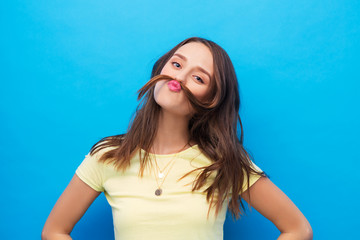 hairstyle and people concept - young woman or teenage girl making mustache with strand of hair over bright blue background © Syda Productions