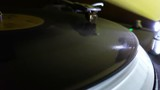 Closeup of a turntable spinning a record LP, with the LED reflecting the spinning grooves.