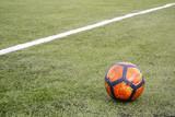 Fototapeta Sport - Soccer ball on grass football field © stanislavss