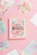 happy mothers day greeting card with flowers, and various mothers day postcards arranged around on pink background