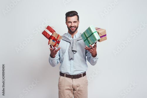 Gifts boom! Cheerful young man is holding gifts and feeling so happy standing on a grey background
