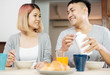 happy asian couple in pajamas sitting at table in kitchen at home in morning and having cereal breakfast together.husband pour milk into wife bowl.