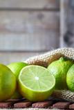 Fresh ripe organic limes on wooden background. Copy space