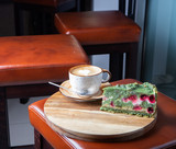 Pistachio cake with raspberries on a wooden tray and a cup of coffee