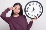 Sleepy young Asian woman with a clock in the morning. - 248878619