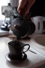 Kawiarka i filiżanka gorącej parującej kawy